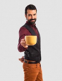 Tragende weste des mannes, die einen tasse kaffee hält