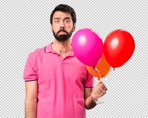Trauriger hübscher junger mann, der ballone hält