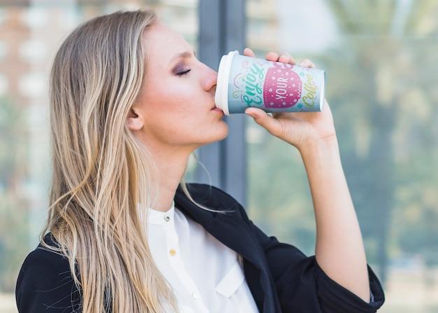 Trinkender kaffee der frau von der plastikschale