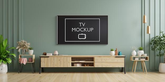 Tv auf schrank im modernen wohnzimmer mit sessel, lampe, tisch, blume und pflanze auf dunkelgrüner wand. 3d-rendering