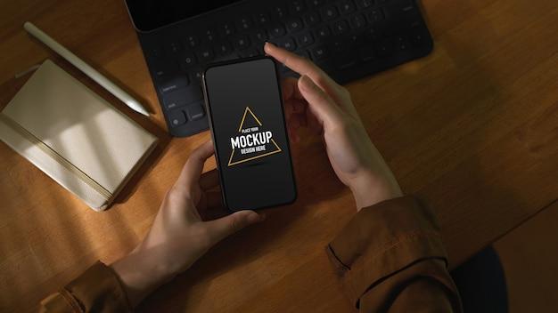 Überkopfaufnahme der frau unter verwendung des modell-smartphones auf holztisch mit tastatur und tagebuch