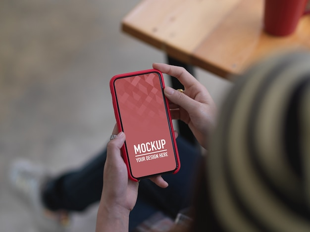 Überkopfaufnahme der frau unter verwendung des modell-smartphones beim sitzen am holztisch im café