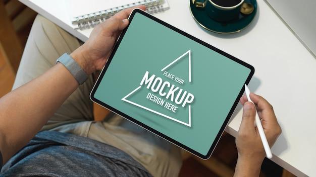Überkopfaufnahme des männlichen büroangestellten, der mit dem digitalen tablet des modells arbeitet