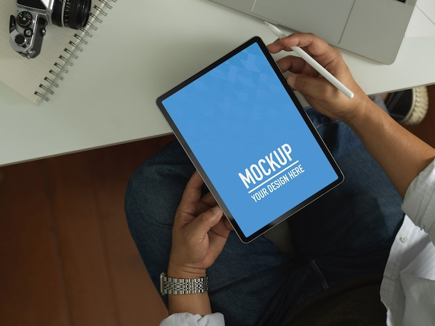 Überkopfaufnahme des männlichen büroangestellten unter verwendung des digitalen tablets schließen beschneidungspfad auf arbeitstisch ein