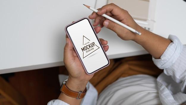 Überkopfaufnahme des männlichen unternehmers, der schein-smartphone beim sitzen am arbeitsplatz hält