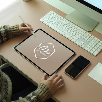 Überkopfaufnahme des weiblichen arbeiters, der mit modell digitalem tablett auf computertisch mit vorräten arbeitet