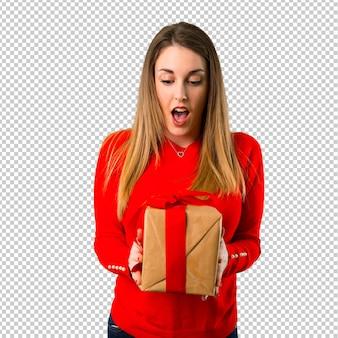 Überraschte junge blonde frau, die ein geschenk anhält