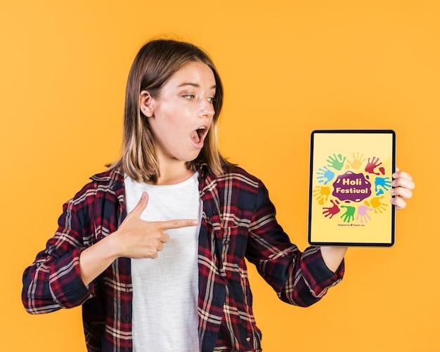 Überraschte junge frau, die finger auf ein tablettenmodell zeigt