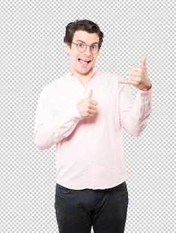 Überraschter junger mann, der eine geste des benennens mit der hand macht