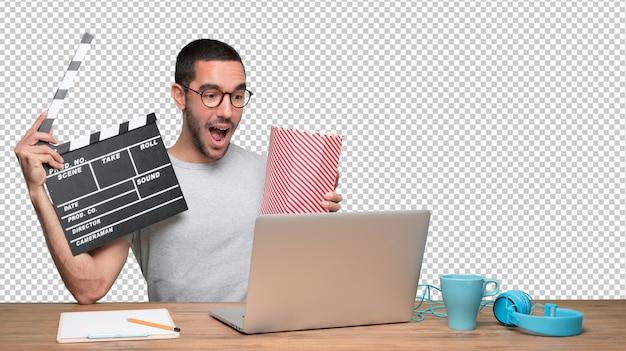 Überraschter junger mann, der einen film auf seinem laptop aufpasst und popcorn isst