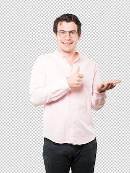Überraschter junger mann, der etwas mit seiner hand hält