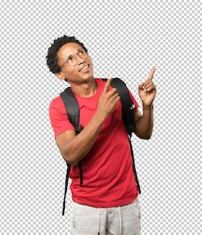 Überraschter junger mann, der oben mit seinem finger zeigt