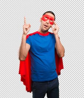 Überraschter superheld, der oben zeigt
