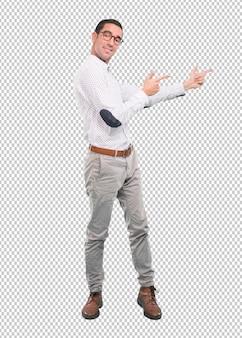 Überzeugter junger mann, der mit seiner hand - voller körperschuß zeigt