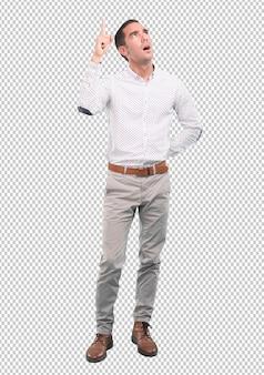 Überzeugter junger mann, der oben mit seiner hand - voller körperschuß zeigt