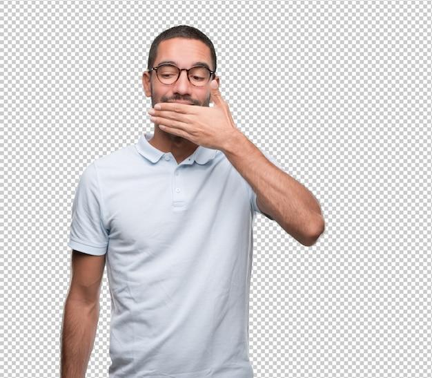 Überzeugter junger mann, der seinen mund mit seiner hand bedeckt