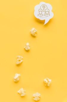 Umgedrehtes fragezeichen aus zerknittertem papier mit chatblase