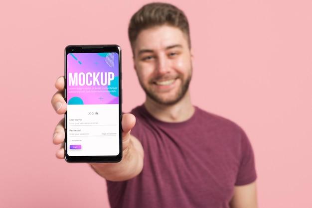 Unscharfer mann, der digitales modell des smartphones zeigt