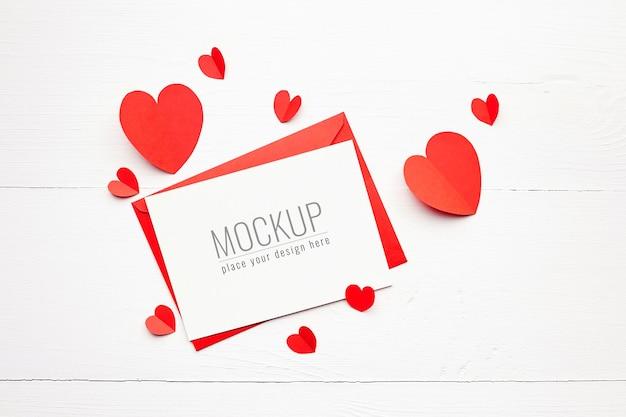 Valentinstagskartenmodell mit roten papierherzen auf weißer holzoberfläche