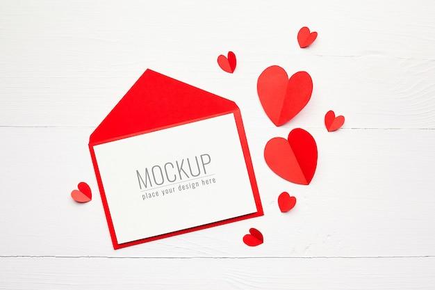 Valentinstagskartenmodell mit umschlag und roten papierherzen auf weißer holzoberfläche