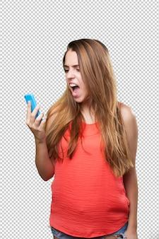 Verärgerte junge frau, die zum mobile schreit