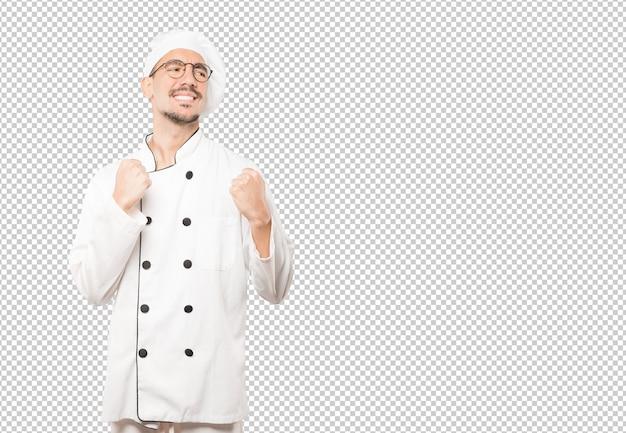 Verärgerter junger koch, der eine wettbewerbsfähige geste tut