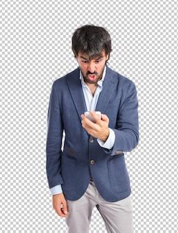 Verärgerter mann, der mit mobile über weißem hintergrund spricht