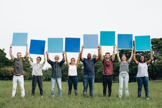 Verschiedene leute, die blaue quadratische bretter im park halten