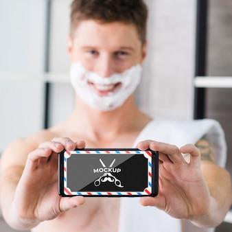 Verschwommener mann, der sich rasiert und handy hält