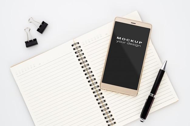 Verspotten sie herauf leeren bildschirm von smartphone auf notizbuch mit stift auf weiß