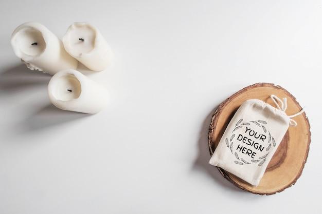 Verspotten sie oben von der baumwolltasche oder -beutel auf hölzernem schnittbaumabschnitt und weißen kerzen auf weißer tabelle