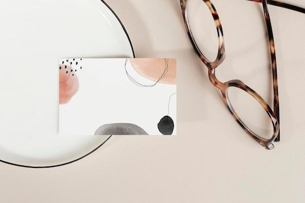 Visitenkarte auf einem teller mit brillenmodell