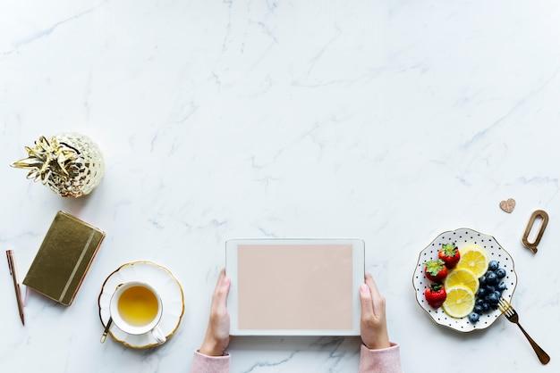 Vogelperspektive der frau, die eine digitale tablette auf einer marmortabelle mit designraum verwendet