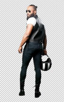 Voller körper des schwarzen motorradfahrers, der einen sturzhelm hält