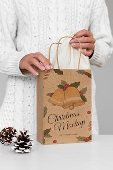 Vorderansicht der frau, die weihnachtspapiertüte mit tannenzapfen hält