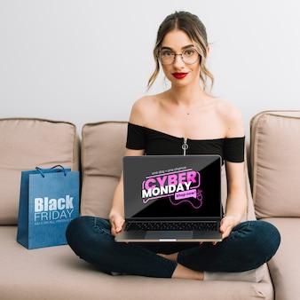 Vorderansicht der frau einen laptop mit cyber-montag-angebot halten