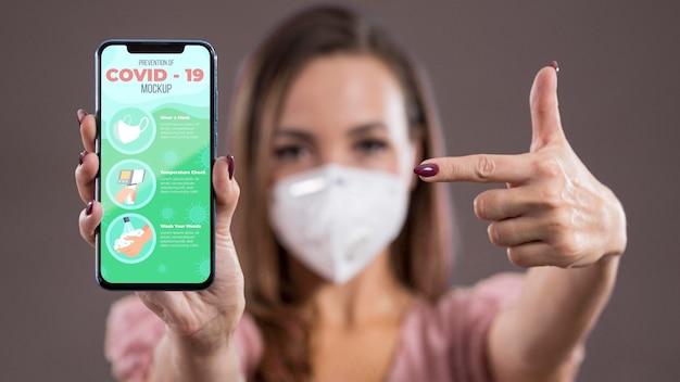 Vorderansicht der frau mit maske, die auf smartphone hält und zeigt