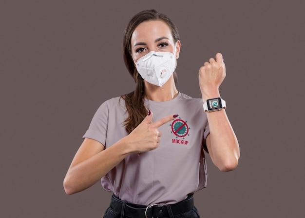 Vorderansicht der frau mit maske, die auf smartwatch zeigt