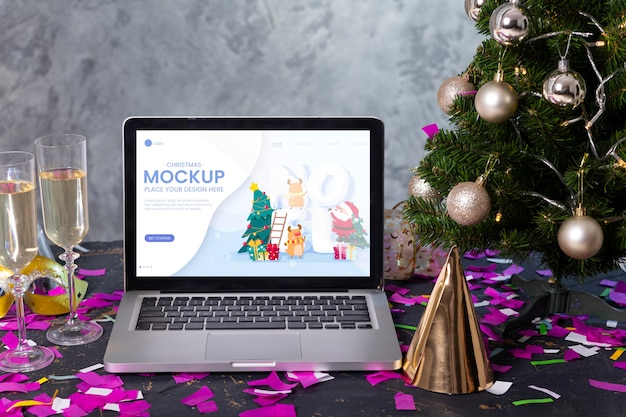 Vorderansicht des laptops mit champagnergläsern und partyhut für neujahrsfeier