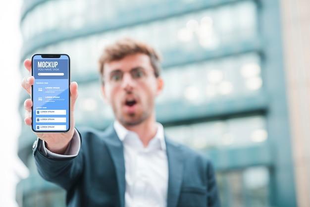 Vorderansicht des schockierten geschäftsmannes, der smartphone hält