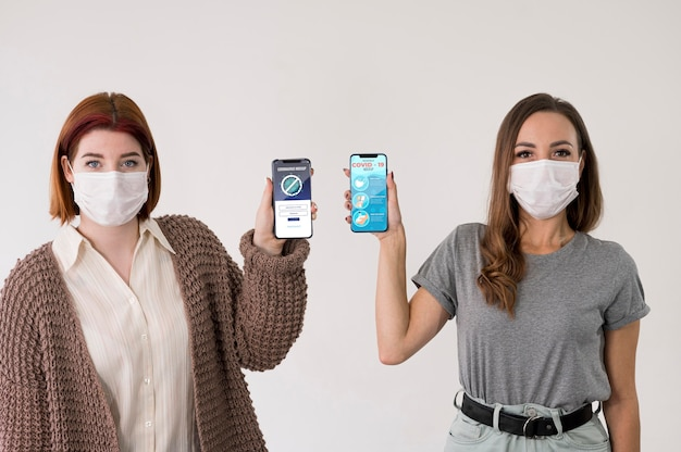 Vorderansicht von frauen mit masken, die smartphones halten
