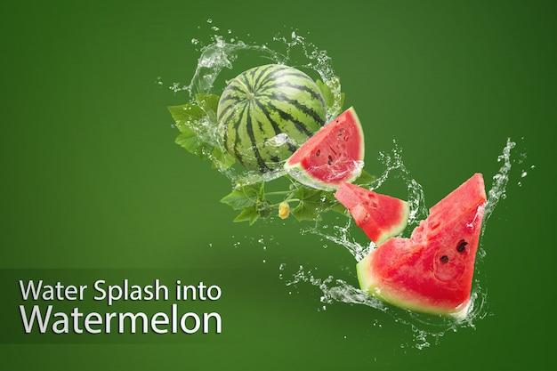 Wasser spritzt auf in scheiben geschnittene wassermelone auf grün