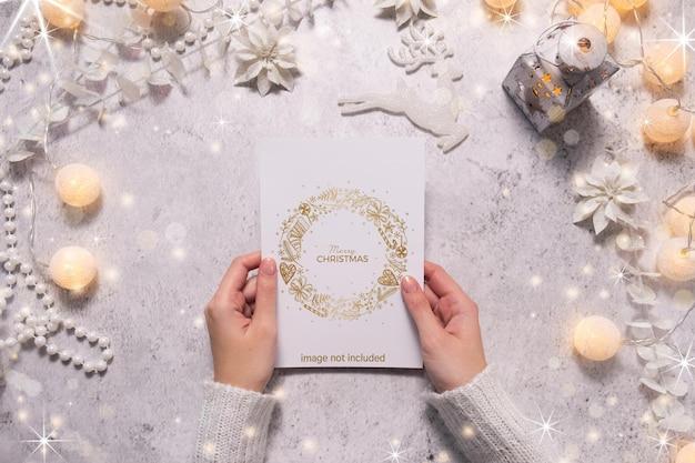 Weibliche hände halten eine weihnachtskarte. festliche atmosphäre während der weihnachtszeit.