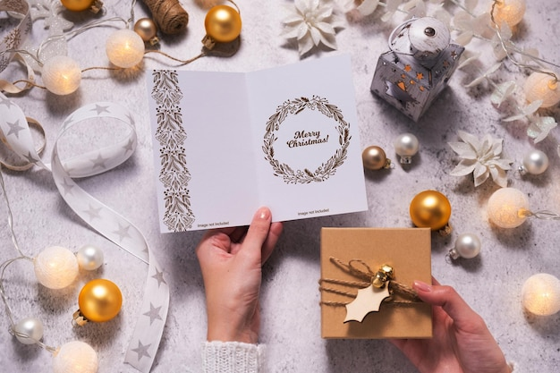 Weibliche hände halten eine weihnachtskarte und eine geschenkbox. umgeben von weihnachtsschmuck und lichtern. attrappe, lehrmodell, simulation