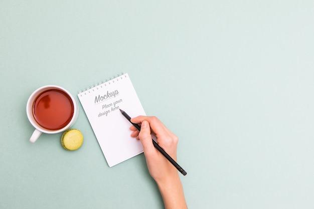 Weibliche hand, die schwarzen bleistift hält und in notizbuchmodell schreibt