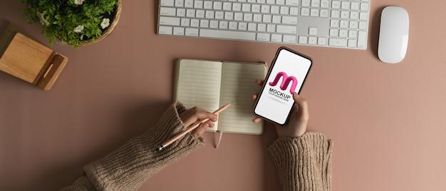 Weibliche hand hält verspottetes smartphone beim schreiben