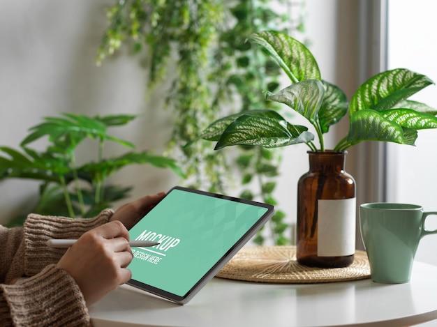 Weibliche hand unter verwendung des digitalen tablettenmodells auf kaffeetisch