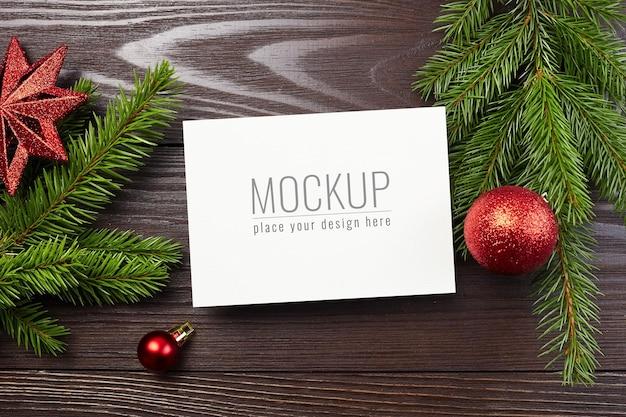 Weihnachts- oder neujahrsgrußkartenmodell mit roten festlichen dekorationen und tannenzweigen