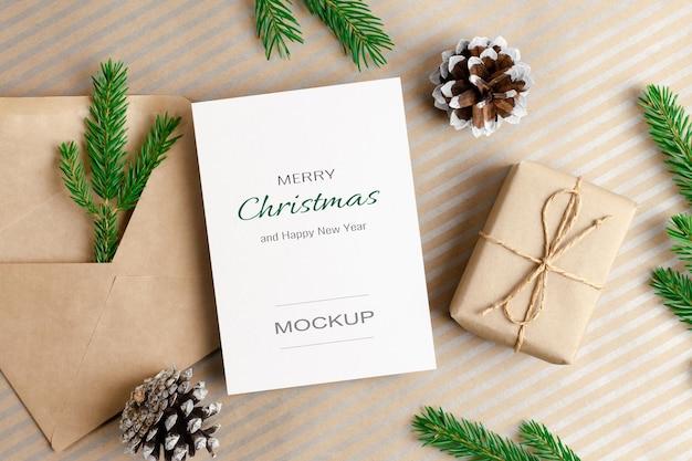 Weihnachts- oder neujahrsgrußkartenmodell mit umschlag, geschenkbox und tannenzapfendekorationen