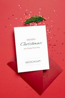 Weihnachts- oder neujahrsgrußkartenmodell mit umschlag und festlichen konfettidekorationen auf rot